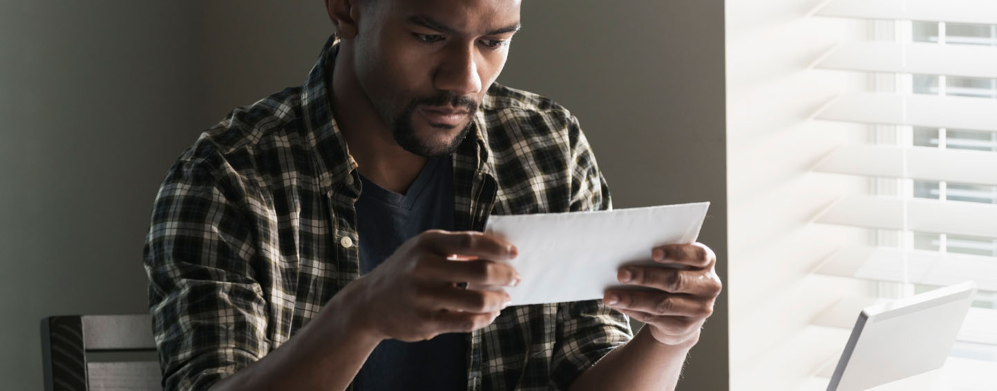 young man sitting at desk holding an envelope with a bill, looks concerned