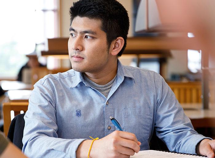 Jirayut Latthivongskorn sitting at a desk, taking notes.
